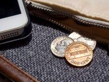 El dólar de EE. UU. acuña colocado fuera de la cartera con smartphone Fotografía de archivo
