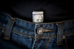 El dólar de EE. UU. cobra adentro el bolsillo de los vaqueros Fotos de archivo