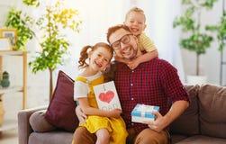 ?El d?a de padre feliz! Los ni?os felicitan al pap? y le dan el regalo y la postal fotos de archivo libres de regalías
