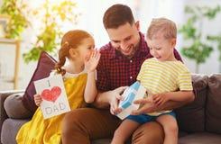 ?El d?a de padre feliz! Los ni?os felicitan al pap? y le dan el regalo y la postal imagen de archivo