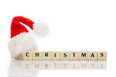 El dado deletreado la Navidad del texto cubica el sombrero santa Fotografía de archivo