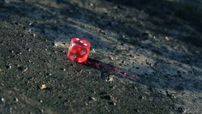 El dado rojo cae en un bloque de cemento en la cámara lenta almacen de video