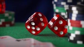 El dado rojo en orden rueda, los microprocesadores del casino, tarjetas en el fieltro del verde almacen de metraje de vídeo
