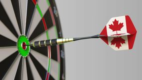 El dardo que ofrece la bandera de Canadá golpea la diana de la blanco Deportes o animación conceptual relacionada del éxito polít almacen de video
