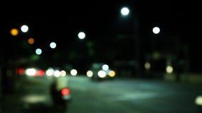 El De enfocó los semáforos de la noche, noche en la ciudad Desenfocado con borroso almacen de video