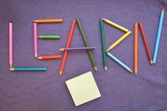 El ` de la inscripción aprende que el ` está escrito en lápices coloreados Fotos de archivo libres de regalías