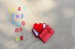 El ` de las palabras apenas el dos de nosotros ` en la arena imagen de archivo