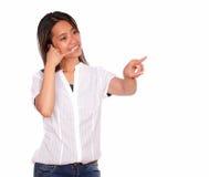 El decir de la mujer joven me llama que señala a su izquierda Imagen de archivo libre de regalías