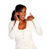 El decir de la mujer me llama mientras que habla en el teléfono celular Fotografía de archivo libre de regalías