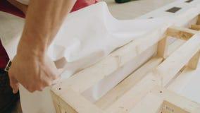 El decorador ata la lona se sujeta con grapa a las decoraciones de madera Primer de las manos del empleado almacen de video