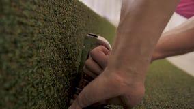 El decorador de trabajo sujeta con grapa césped artificial al paisaje que miente en el piso Manos del primer almacen de metraje de vídeo