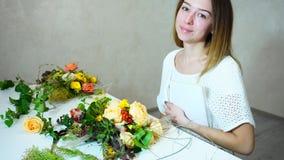 El decorador floral de sexo femenino maravilloso mira la cámara y las sonrisas, sentándose en la tabla con los ramos florales en  almacen de video