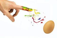 El dedo asperja la pintura sobre el huevo en blanco Imágenes de archivo libres de regalías