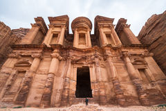 El Deir or The Monastery at Petra, Jordan. A person standing in the doorway of the Monastery at Petra, Jordan, shows the enormity of the ancient building's Stock Image