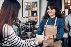 El delantal asiático de la mezclilla del desgaste del barista de la mujer que sostenía la taza de café sirvió a fotos de archivo libres de regalías