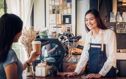 El delantal asiático de la mezclilla del desgaste del barista de la mujer sirvió ir taza de café a imagenes de archivo
