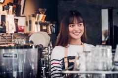 El delantal femenino asiático de la mezclilla del desgaste del barista en la barra contraria con la cara de la sonrisa, concepto foto de archivo