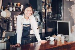 El delantal femenino asiático de la mezclilla del desgaste del barista pone su mano en b contrario foto de archivo libre de regalías