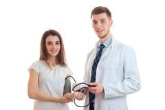 El delantal hermoso joven del doctor toma la presión de su paciente Imagen de archivo libre de regalías