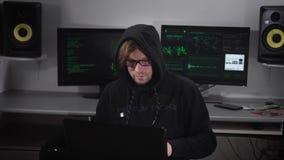 El delincuente del pirata informático realiza ataques cibernéticos clandestinos con el uso de un ordenador portátil con software  metrajes