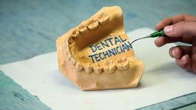 El dentista anota el texto en gomas de los artificials almacen de metraje de vídeo