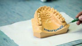 El dentista anota el texto en gomas de los artificials metrajes