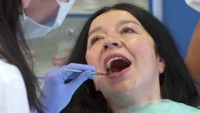 El dentista comprueba encima de los dientes del ` s de la mujer metrajes