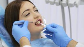 El dentista con las muestras del color del diente est? eligiendo la sombra para los dientes pacientes de la mujer almacen de metraje de vídeo