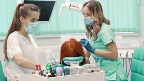 El dentista de la mujer lleva al paciente a la clínica dental almacen de video