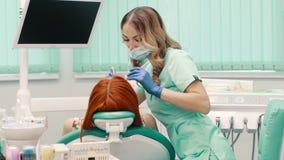 El dentista de sexo femenino trata a la mujer del paciente de los dientes metrajes
