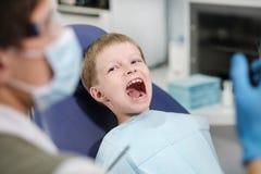 El dentista de sexo masculino examina los dientes del muchacho alegre paciente foto de archivo