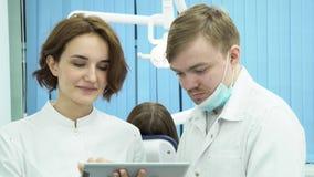 El dentista de sexo masculino y el ayudante femenino discuten la diagnosis del paciente media Los dentistas de la mujer y del hom almacen de video