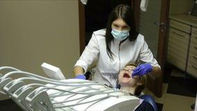 El dentista del diente trata a una mujer en su oficina almacen de metraje de vídeo