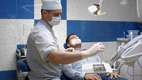 El dentista detecta los dientes cariados del paciente en la silla del dentista Foto de archivo