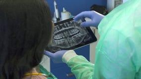 El dentista enfoca imagen de la radiografía en su tableta imagenes de archivo