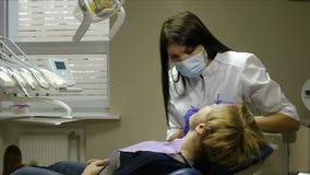 El dentista examina y trata a la mujer en su oficina almacen de video