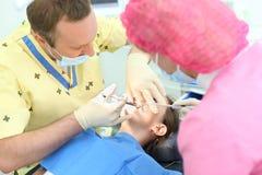 El dentista hace la inyección a la muchacha que se sienta en silla Foto de archivo libre de regalías