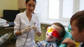 El dentista joven se prepara para una sesión del tratamiento Un pequeño paciente se sienta en una silla y espera Su hermano gemel almacen de video