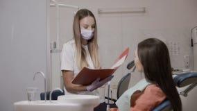 El dentista lee a un paciente los precios para los dientes del tratamiento almacen de metraje de vídeo