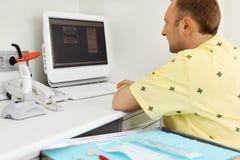 El dentista mira radiografías de la quijada el monitor del ordenador Imagen de archivo libre de regalías