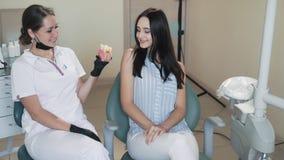 El dentista muestra al modelo paciente del diente con la carie y del diente sano, cámara lenta almacen de video