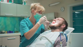 El dentista que examina los dientes pacientes del ` s, lo explica procedimiento almacen de video