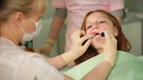 El dentista que mantiene una jeringuilla sus manos asperja un líquido de consolidación en sus dientes metrajes