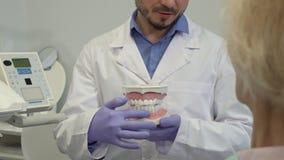 El dentista señala sus fingeres en dientes más bajos en la disposición almacen de video