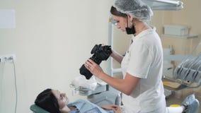 El dentista toma la foto de la boca paciente después del tratamiento dental, cámara lenta metrajes