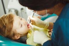 El dentista trata los dientes del paciente joven Reglas de prevención de la carie imagen de archivo libre de regalías