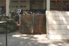El depósito de chatarra al aire libre sucio del patio trasero del garaje del estudio con Rusty Old Zinc Doors, blanco pintó el bo imagenes de archivo