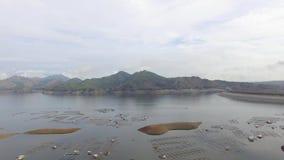 El depósito eléctrico hidráulico de la presa forma el lago enorme en Cordillera montañosa en donde prospera la aguamarina la pisc almacen de metraje de vídeo