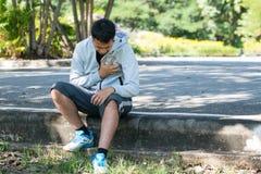 El deportista asiático con dolor de pecho se sentó después de correr en el PA Fotografía de archivo libre de regalías