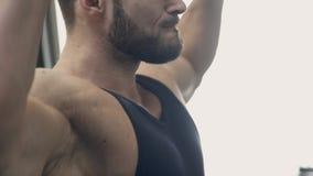 El deportista coloca y levanta pesos en la parte inferior y por encima en gimnasio